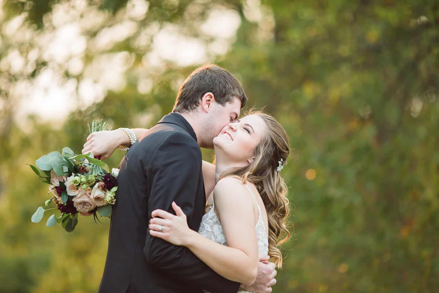 Bride and groom romantic fall photos at Enchanted Acres wedding venue Harrisonville