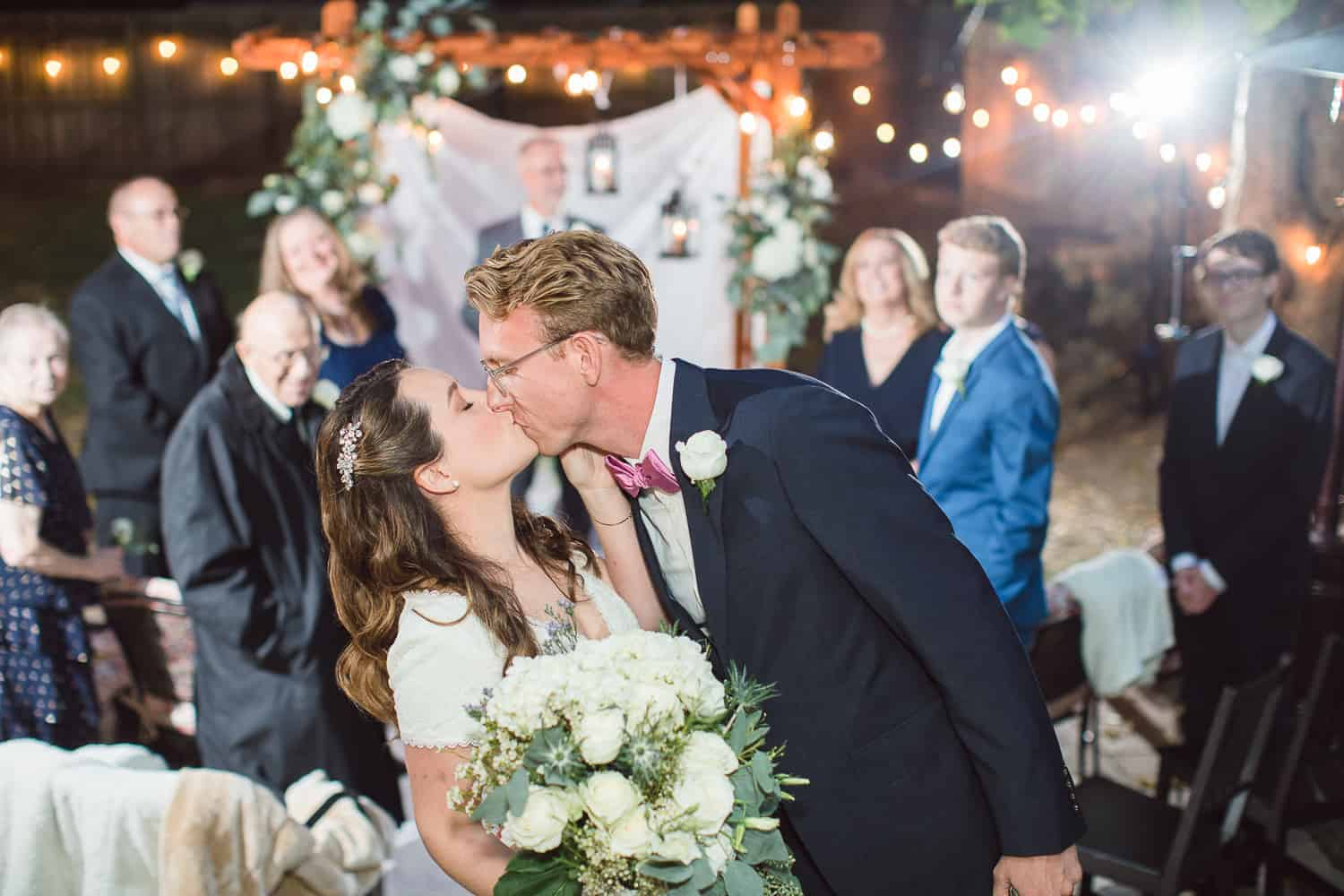 First kiss at night wedding ceremony outdoors